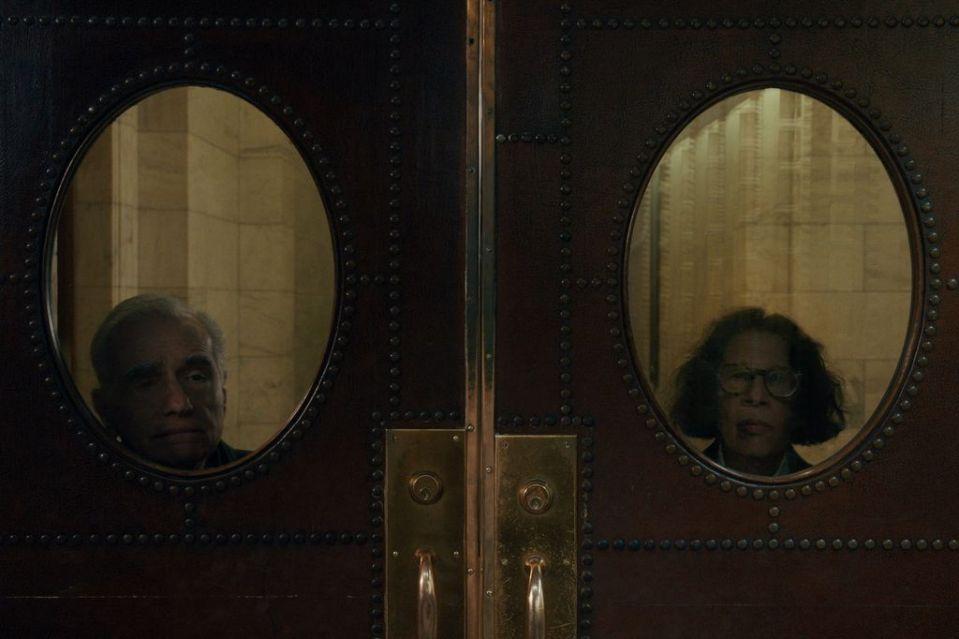 Imagem da série Faz de Conta que NY é uma Cidade. A fotografia é feita na frente de uma porta de madeira que tem duas berturas ovais de vidro, uma de cada lado. Através do vidro do lado esquerdo, podemos observar o rosto do diretor Martin Scorsese. Ele é branco, tem olhos escuros e cabelos grisalhos, e seu rosto está levemente inclinado para o lado direito da imagem, onde ele parece observar algo com um olhar curioso. Na abertura da esquerda, podemos observar a escritora Fran Lebowitz, que é branca, tem cabelos escuros onsulados e volumosos na altura do queixo. Ela olha diretamente para a câmera com uma expressão séria.