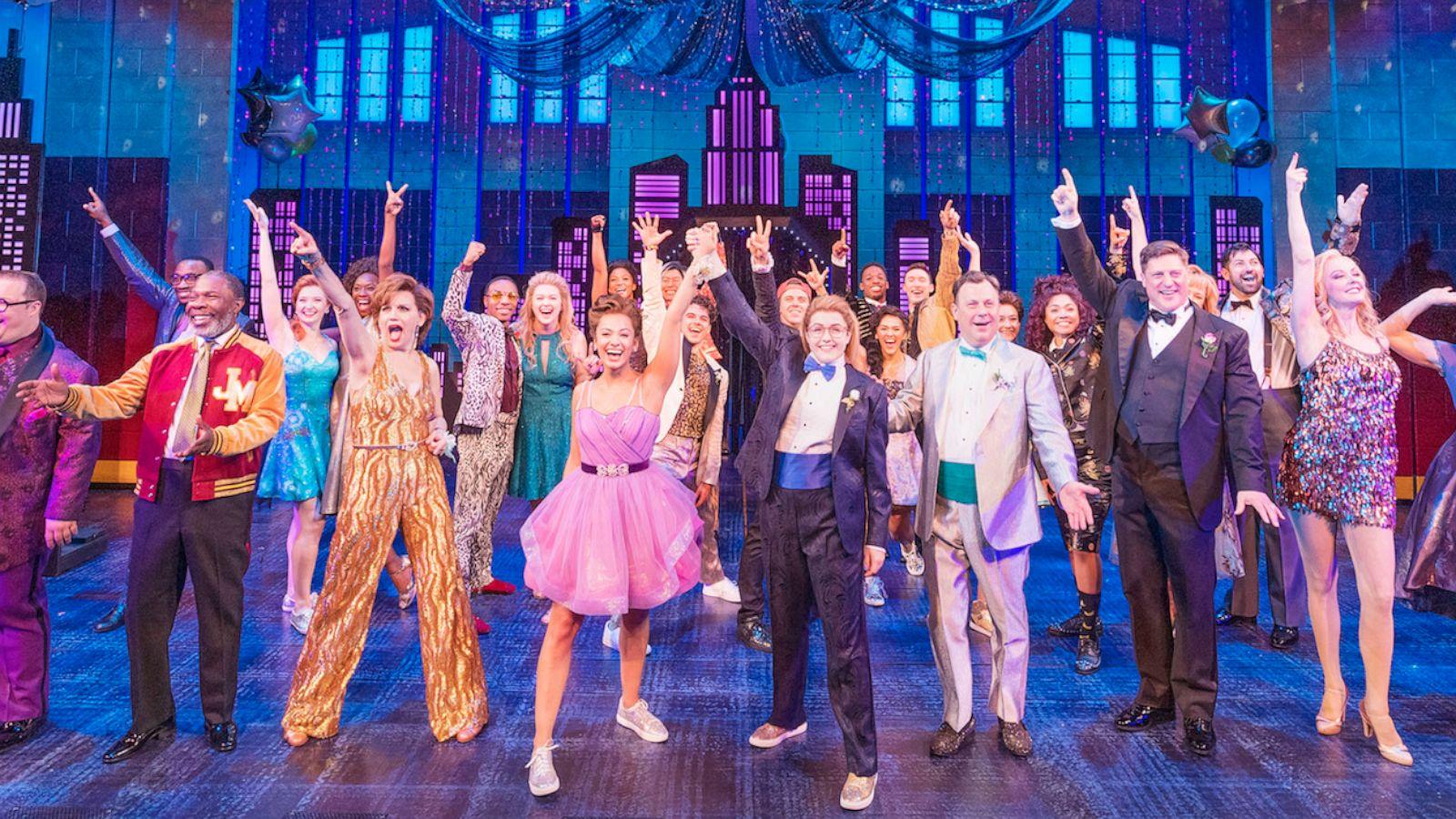 Imagem da peça de teatro The Prom. Mostra vários atores com os braços para o alto durante uma canção.
