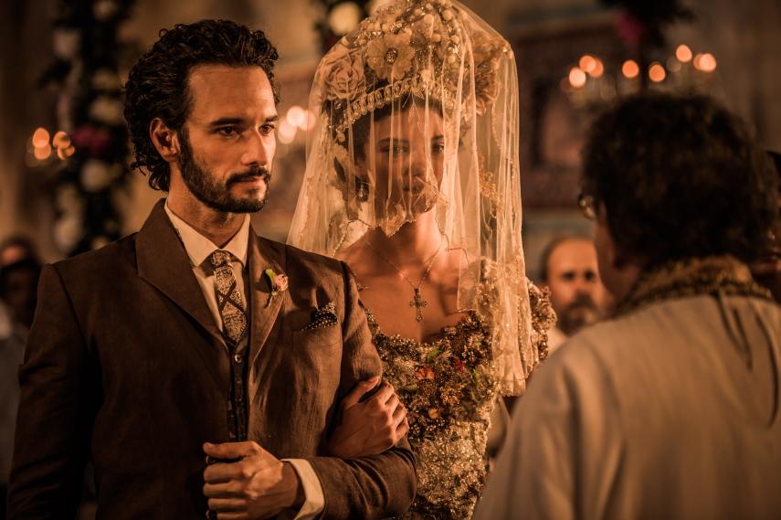 Cena da novela Velho Chico. Na imagem, vemos a cerimônia de casamento do Coronel Afrânio Sá Ribeiro e Leonor. O Coronel está no altar, trajando um terno marrom, ao lado da sua noiva, que usa um véu transparente sobre o rosto.