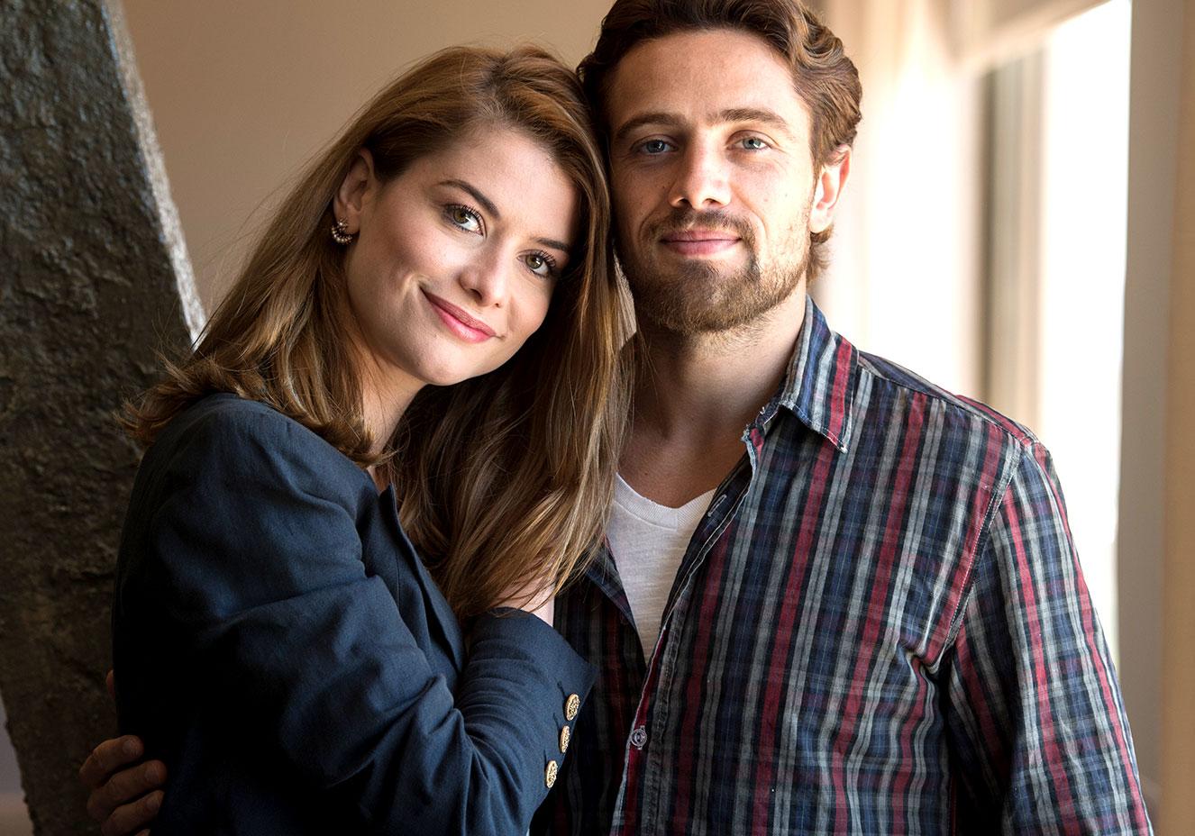 Texto alternativo: Há um casal na foto. Um homem branco, loiro, de barba está a esquerda, com uma camisa xadrez azul e vermelha. A seu lado está uma mulher branca, loira, com um blazer azul. Ela está abraçando o homem de lado.
