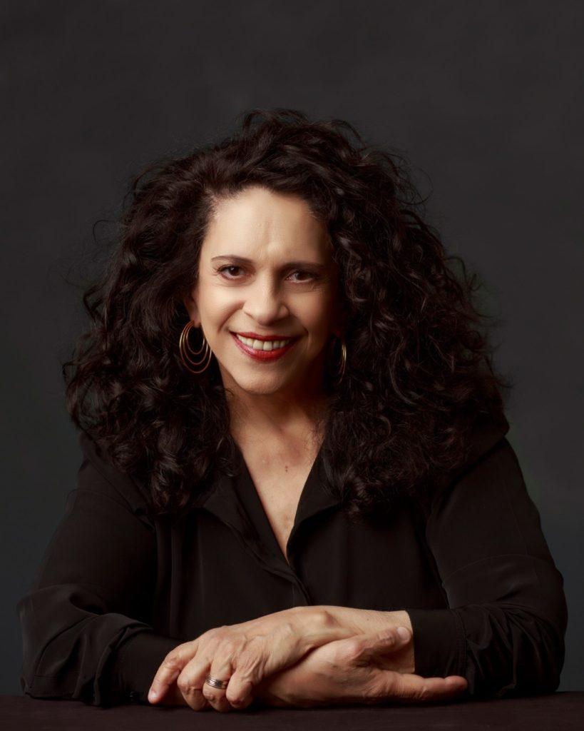[Foto da cantora Gal Costa. Gal é uma mulher branca de cabelo preto na altura dos ombros. Ela veste um vestido preta e o fundo da fotografia também é preto. Suas mãos estão entrelaçadas. Ela usa brinco de argola dourada e batom vermelho]