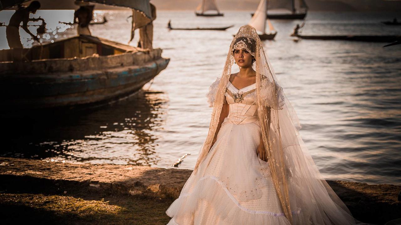 Cena da novela Velho Chico. A jovem Tereza, parada, usa um longo vestido branco de noiva, prestes a casar-se com o político Carlos Eduardo. Ao fundo, vemos uma embarcação de pescadores, no Rio São Francisco.