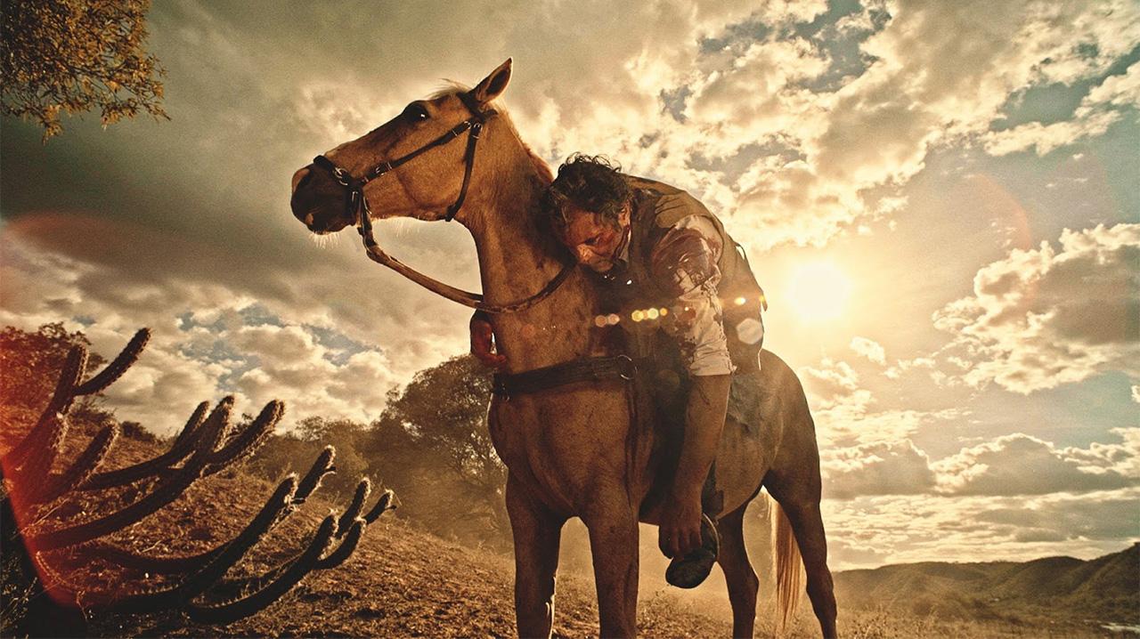 Cena da novela Velho Chico. Santo, enquanto cavalga, é alvejado por um tiro no ombro. No fundo, vemos o céu luminoso, entre nuvens, e a paisagem da caatinga.