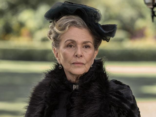 Uma mulher branca, idosa, de cabelos brancos, vestida com um casaco de pele preto e um chapéu pequeno.
