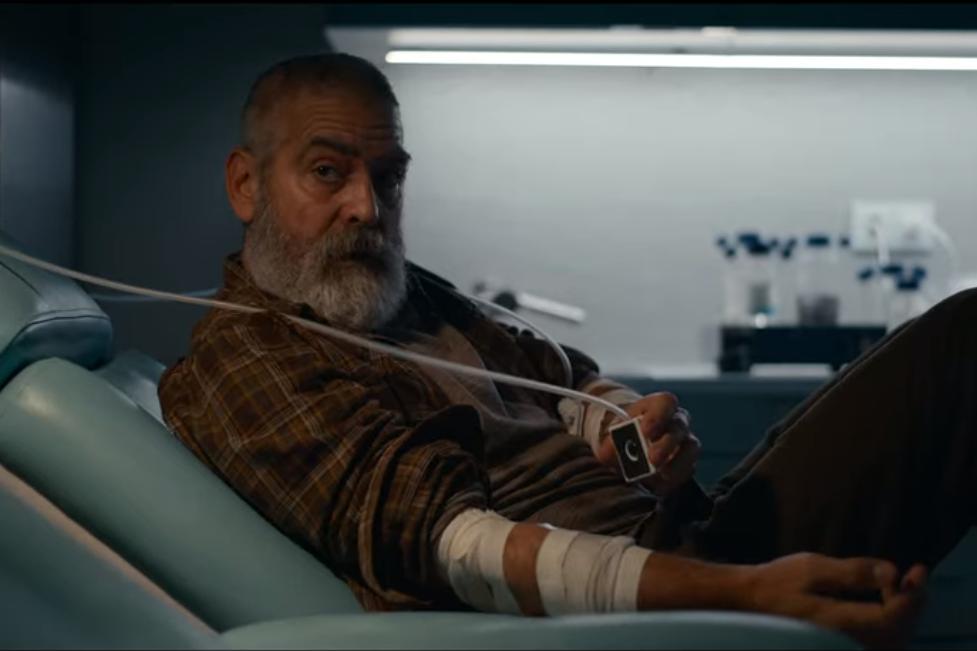 Cena de O Céu da Meia Noite. Vemos George Clooney, que interpreta Augustine de lado. Ele é um homem branco, de cabelo branco curto e barba comprida, também branca. Está se deitando com o tronco virado para cima, rosto e olhos em direção à borda esquerda da imagem. Em sua mão esquerda, sobre a barriga, há um pequeno objeto quadrado ligado a um cabo branco que se estende até a borda esquerda da imagem. Seu braço direito tem duas faixas brancas enroladas e está em repouso sobre a cama de hospital. A cor da cama e a parede que está atrás de Augustine é azul, enquanto a sua roupa e pele têm um tom amarronzado.