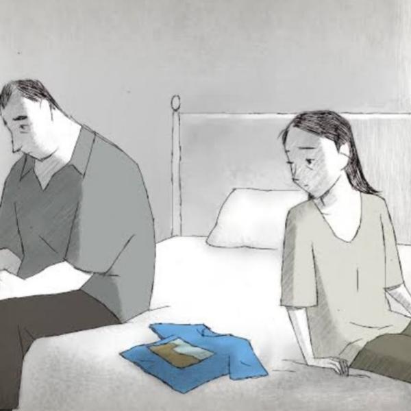 Cena do curta-metragem Se Algo Acontecer...Te Amo. Na animação, há uma mulher adulta de cabelo liso sentada em uma cama. Ela olha para uma camiseta azul com desenho, que está estendida ao seu lado. Ao lado da camiseta, há um homem adulto cabisbaixo. O desenho está em tons frios de cinza.
