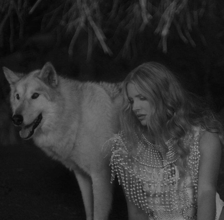 Capa do single Chemtrails Over the Country Club. A imagem mostra Lana Del Rey, abaixada, ao lado de um lobo branco. Ela veste uma roupa com um babado de pérolas, e olha em direção ao lado esquerdo. O fundo é uma floresta escura. A imagem recebeu um tratamento para ficar em preto e branco.