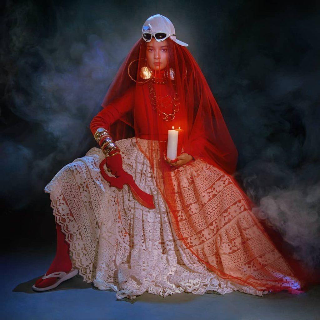 Capa do CD Rito de Passá. A imagem mostra MC Tha sentada, ao centro. Ela veste um véu vermelho e uma saia branca de renda. Ela veste chinelo de dedo nos pés, e está com um boné e um óculos branco apoiados na cabeça. Na mão esquerda segura uma adaga vermelha. Na mão direita, segura uma vela branca. O fundo é preto e com fumaças.