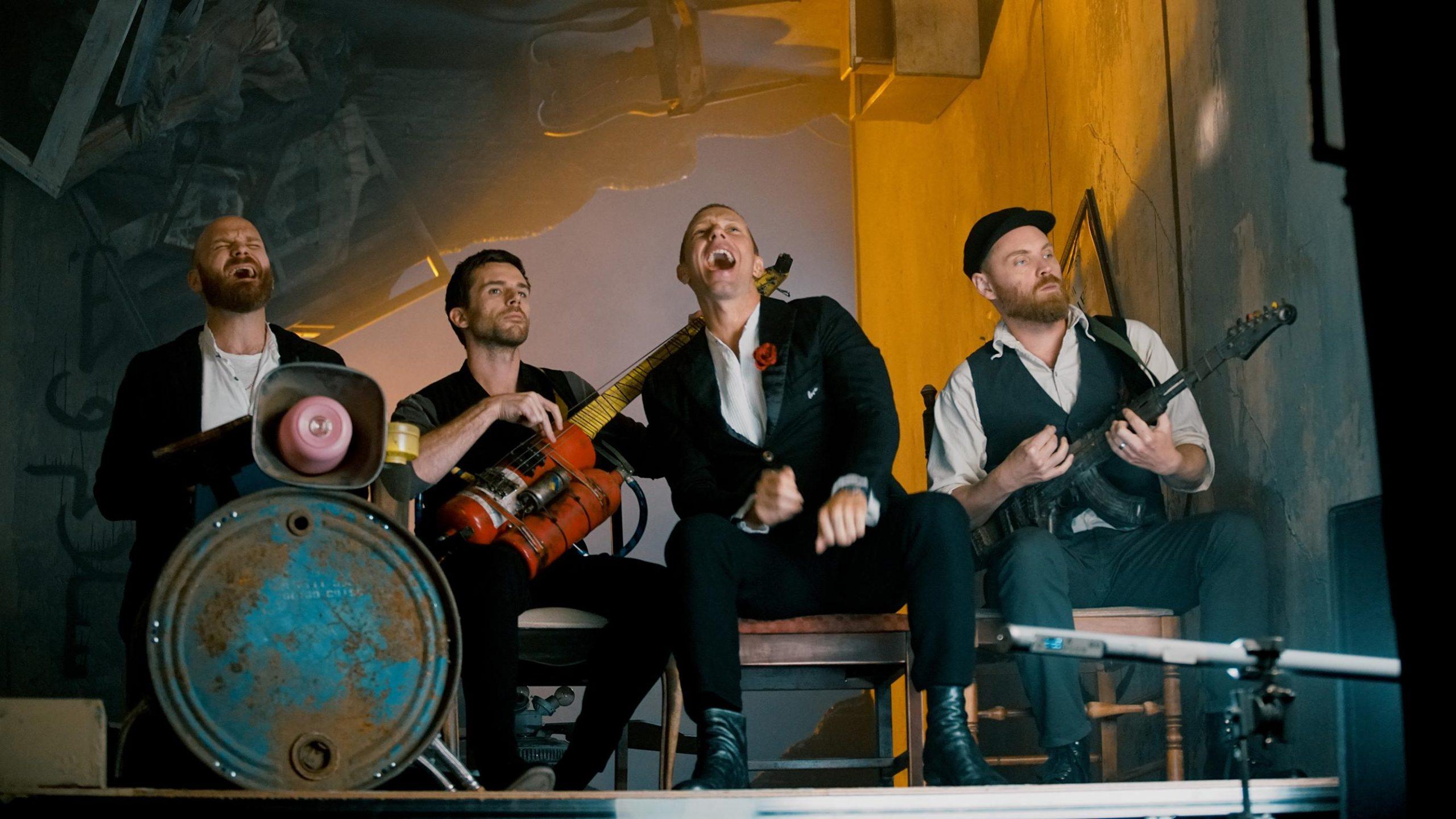 Fotografia colorida da banda Coldplay. Os quatro membros da banda estão sentados em cadeiras de madeira lado a lado em cadeiras de madeira segurando seus instrumentos dentro de uma sala. Primeiro, à esquerda, está Will Champion, um homem branco, careca e de barba ruiva, que veste uma camisa branca e um blazer preto. Ele está cantando, de olhos fechados, e tocando o surdo da bateria que tem uma estampa de mapa-mundi. Ao lado dele, está o baixista Guy Berrymen, um homem branco de barba e cabelos curtos castanho escuros. Ele toca seu instrumento, que é alaranjado, e veste uma camisa de manga longa e calças pretas. Ao lado dele, está o vocalista Chris Martin, um homem branco de cabelos loiros e olhos azuis. Ele está cantando, olhando para cima, vestindo um terno preto com uma rosa vermelha no bolso do paletó. Depois dele, no lado direito da imagem, está o guitarrista Johnny Buckland, um homem branco de cabelos ruivos. Ele toca seu instrumento olhando para o lado direito da imagem e veste uma camisa branca e um colete preto. A sala em que a banda está tem paredes cinzas e uma iluminação amarelada atrás deles.