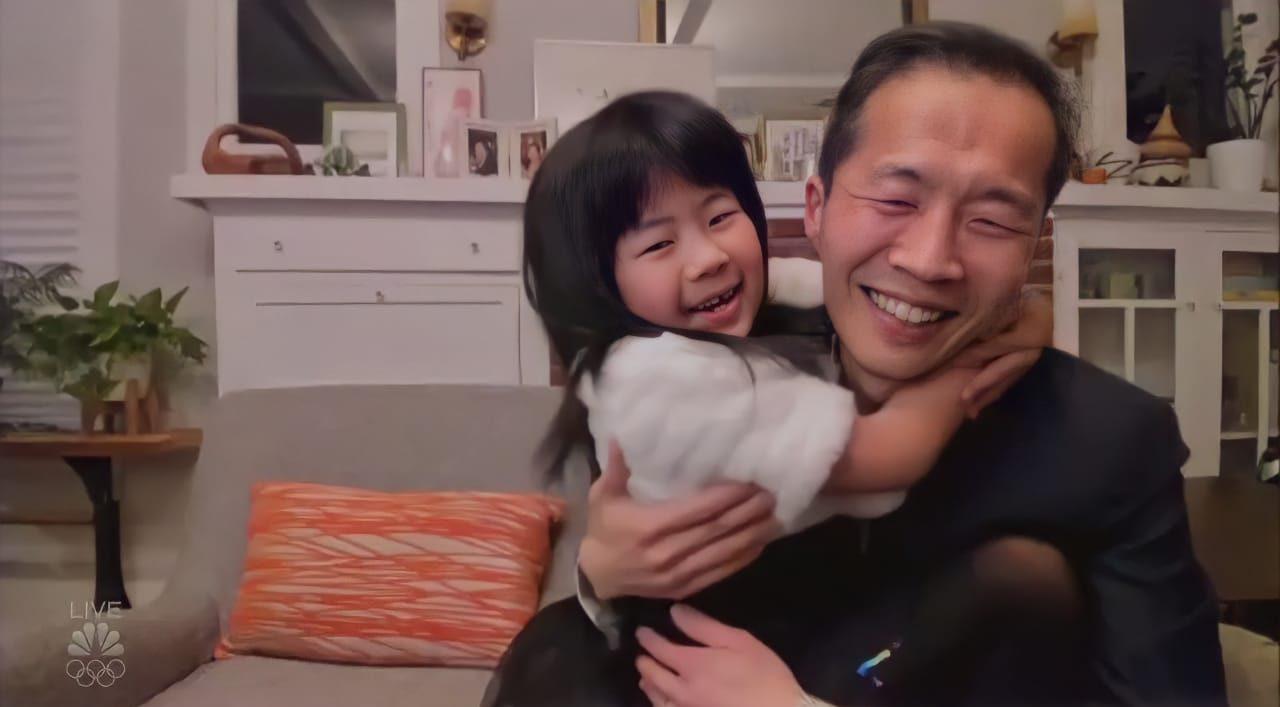 Lee Isaac Chung e sua filha estão em um sofá cinza, ela sentada no colo do pai o abraçando, ambos sorrindo. Atrás deles é possível ver um móvel brano, com porta retratos e outras decorações. No canto da foto há ainda um pequeno vaso de planta em cima de uma mesinha.