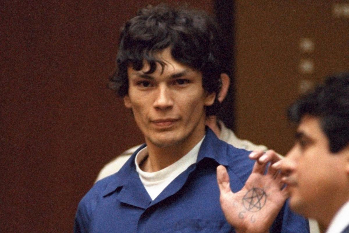 Cena da série Night Stalker: The Hunt For a Serial Killer. Na cena, vemos o assassino Richard Ramirez, um homem hispanico de pele clara e cabelos pretos, sendo levado embora de um tribunal. Ele estende a palma da mão esquerda, que mostra a tatuagem de um pentagrama.