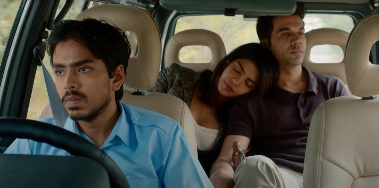 Cena do filme O Tigre Branco. Balram está no banco da frente dirigindo, enquanto Ashok e Pinky estão no banco de trás, ela dorme com a cabeça no ombro dele. Balram é um jovem indiano, de pele marrom, cabelos e bigodes pretos. Ele usa uma camisa azul e está de cinto de segurança. Ashok é um homem indiano, de pele marrom, topete preto, camisa escura e calça bege. Pinky é uma mulher indiana, de pele marrom, cabelo preto e regata branca. O carro tem bancos claros, cor bege.