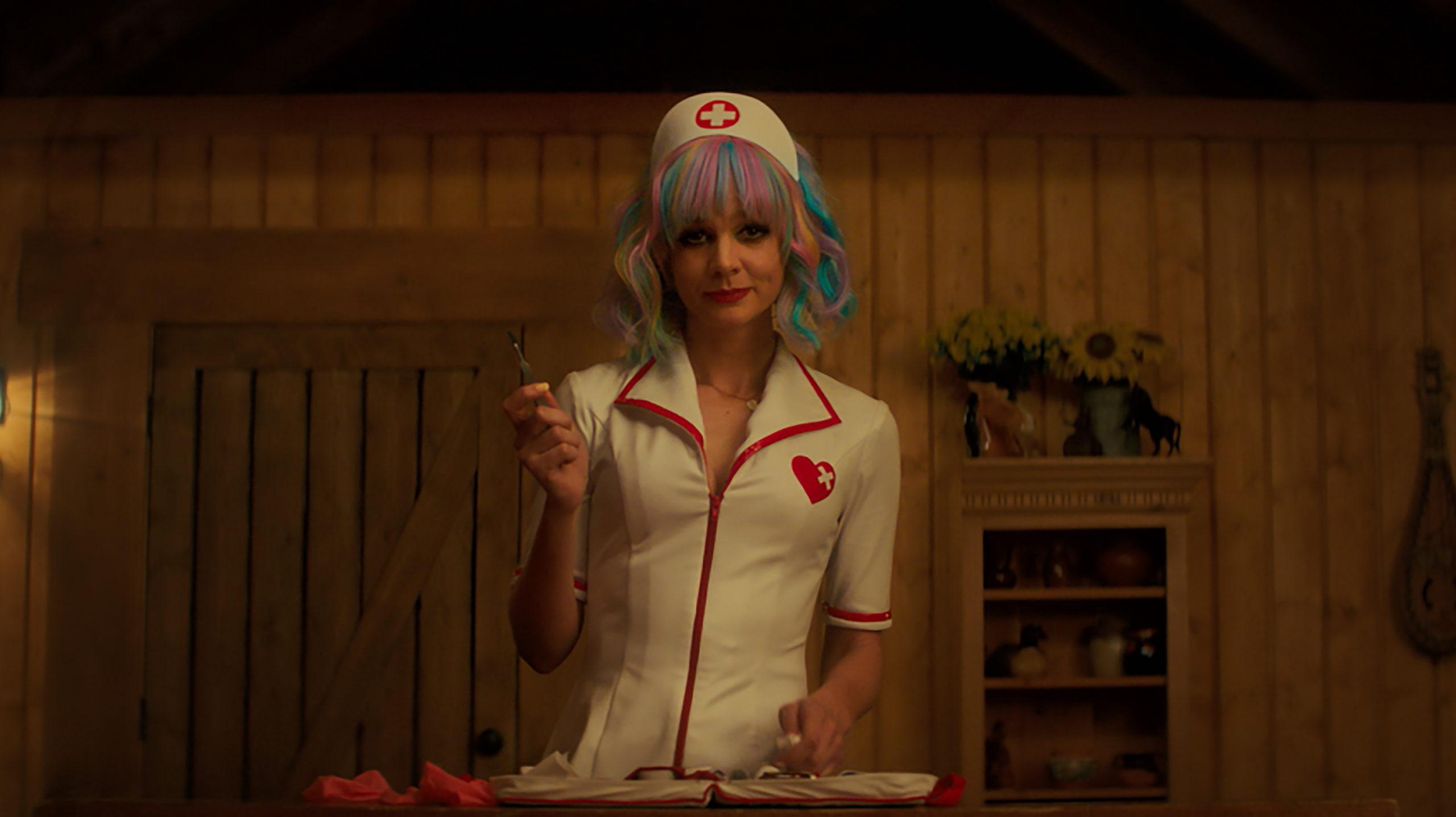 Imagem do filme 'Bela Vingança'. Ao centro da imagem, está a atriz Carey Mullingan enquanto a personagem Cassie. Ela tem a pela branca e está vestindo uma fantasia de enfermeira e está de frente para a câmera, fotografada da cintura para cima. Ela usa uma peruca de mechas colorida em tons pastéis, num comprimento curto, ondulado e uma franjinha. A personagem segura um bisturi em sua mão direita e sorri levemente para a câmera. Ela está usando uma maquiagem preta forte nos olhos e um batom vermelho. A parsonagem está num quadro de parede de madeira, visíveis ao fundo da imagem.