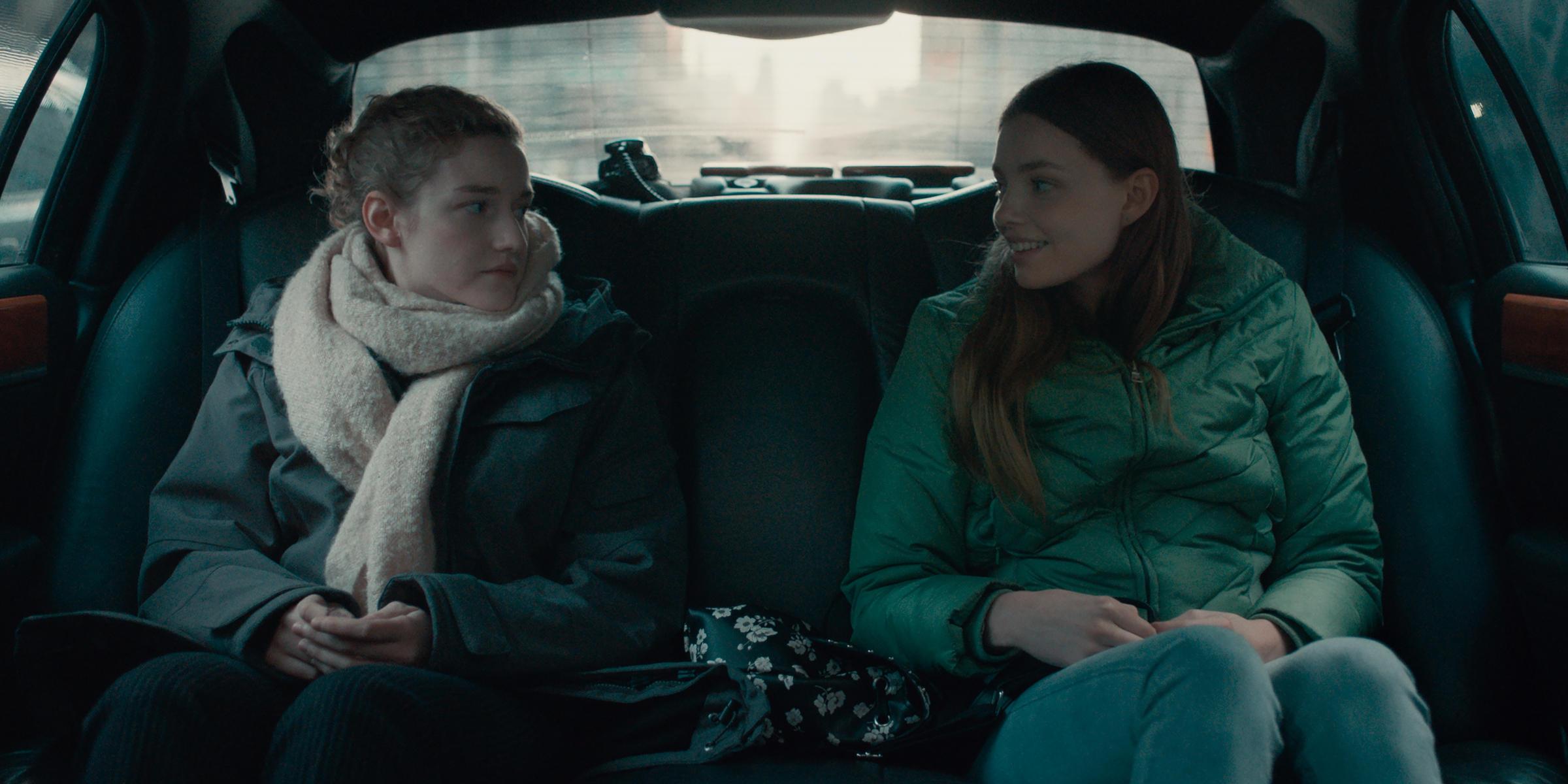 A imagem é uma cena do filme A Assistente. Nela, está a atriz Julia Garner, que interpreta a personagem Jane, e a atriz Kristine Froseth, que interpreta Sienna. Ambas estão sentadas no banco de trás de um carro, uma olhando para a outra. Jane é uma mulher branca, de olhos azuis, cabelos loiros e amarrados em um coque, ela veste um casaco cinza, um cachecol bege e calça preta. Sienna é uma mulher branca, de olhos azuis e cabelos castanhos claros, longos e lisos, ela veste um agasalho verde e uma calça jeans clara.
