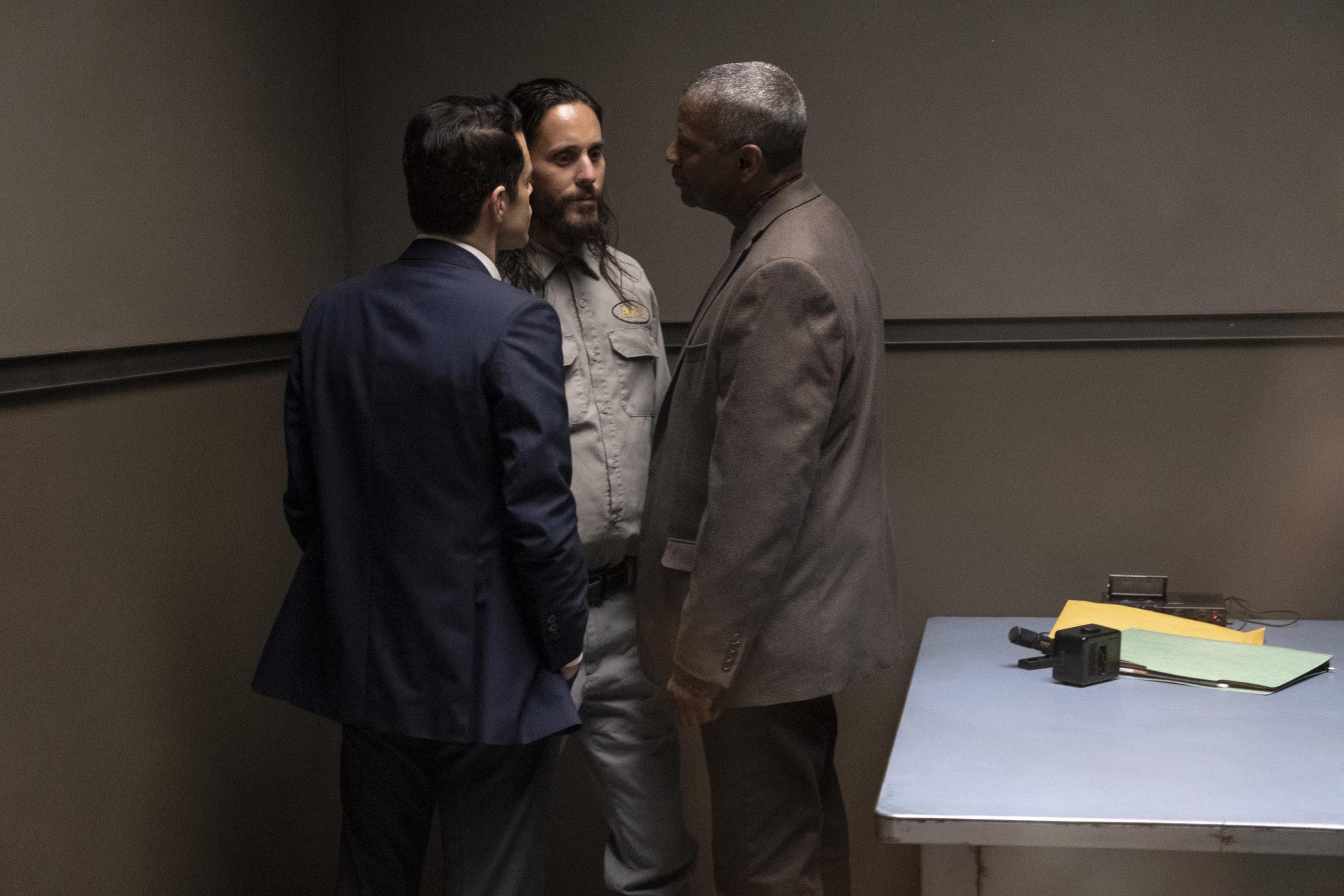 Cena do filme The Little Things. Denzel Washington e Rami Malek encurralam Jared Leto no canto da sala de interrogatório. Denzel é um homem negro de mais de 60 anos, cabelos grisalhos, roupa de policial, bege. Rami é um homem egipcío de 30 anos, veste terno. Jared é um homem branco, de barba e cabelos longos, ele usa roupas cinzas.