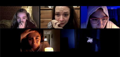 Cena do Filme Host. Na imagem está representada uma tela de uma videoconferência feita pelo zoom, com cinco telas de computador. Da direita para esquerda, e de cima para baixo, a primeira tela, uma mulher de expressão assustada que possui cabelos loiros numa maria chiquinha e pele clara. Na segunda, uma mulher assustada com a mão no rosto, ela possui cabelo castanho longo e pele clara. Na terceira, uma mulher com o rosto parcialmente na tela, ela possui traços asiáticos, usa óculos, cabelo preto liso e pele clara. Na quarta, uma mulher com a mão na testa e expressão aflita, ela tem cabelos castanhos ondulados e pele morena. Na última tela, apenas uma mão está representada, apontando para um corredor escuro.