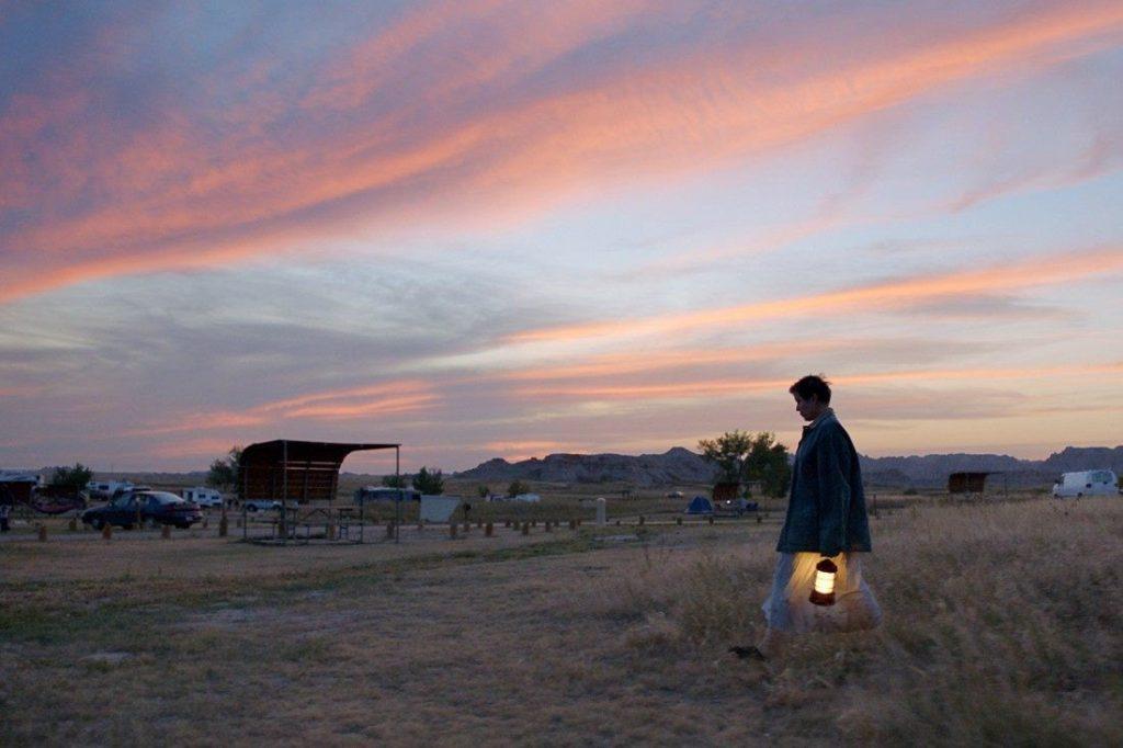 Cena do filme Nomadland. A imagem é ampla e se situa em um deserto. No chão, existe uma grama seca e o céu está colorido em tons de azul, rosa e lilás, enquanto o sol se põe. No canto direito, vemos uma mulher carregando uma lamparina, vestindo um casaco preto e caminhando em direção ao lado esquerdo da imagem. Ao fundo da imagem, existe uma tenda e alguns carros estacionados.
