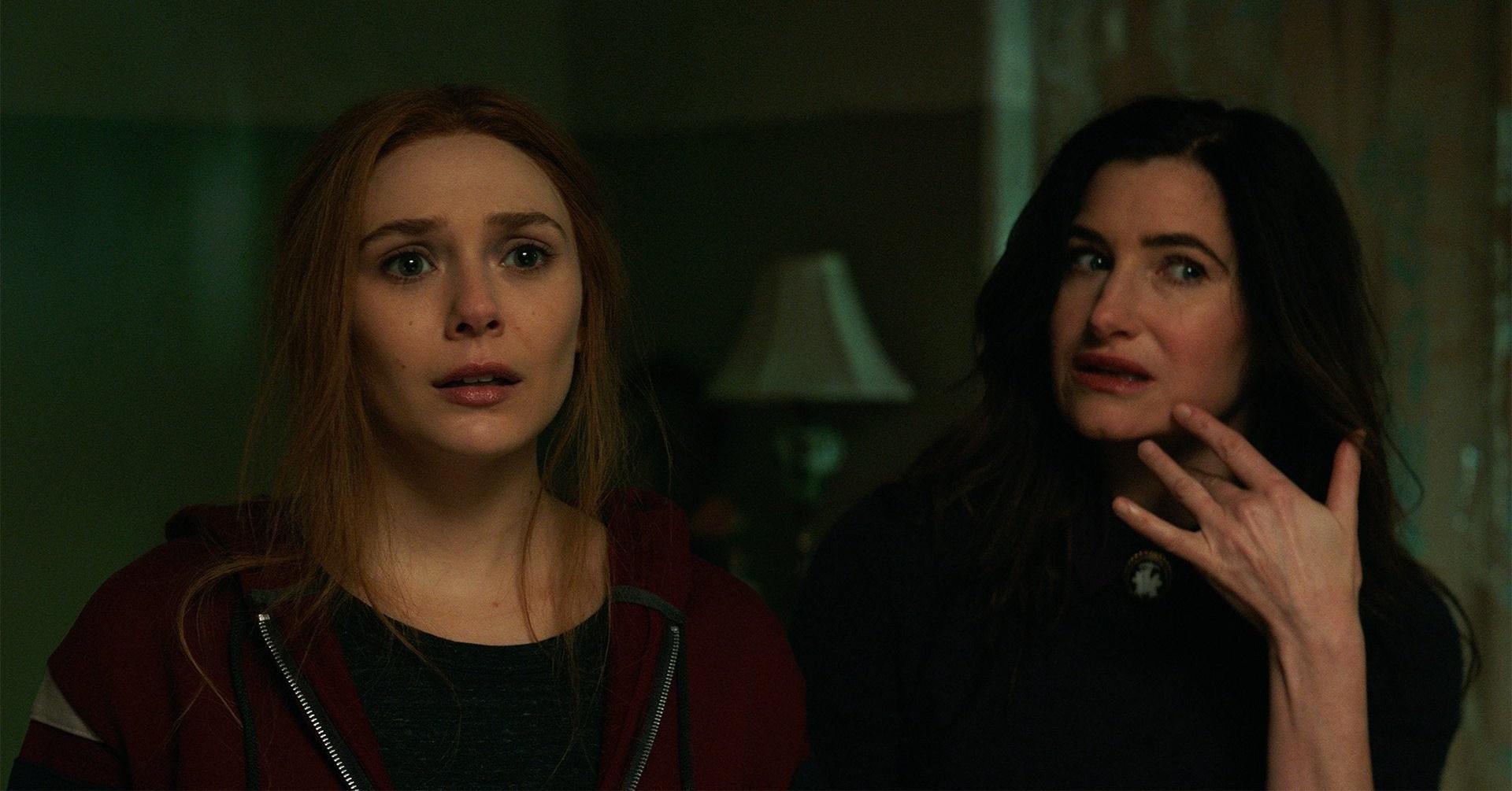 Cena da série WandaVision. Nela, vemos Elizabeth Olsen no papel de Wanda e Kathryn Hahn no papel de Agnes. Elas estão uma ao lado da outra, olhando para a frente. Wanda é uma mulher branca, adulta, ruiva e que veste um moletom vermelho. Agnes é uma mulher branca, adulta, de cabelos pretos e que veste roupas escuras. Ela está com a mão direita no queixo e tem um olhar de dúvida.