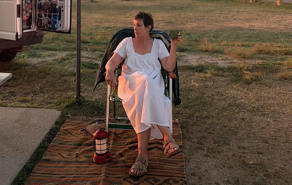 Cena do filme Nomadland. Vemos Fern, interpretada por Frances McDormand, uma mulher branca, de sessenta anos e cabelos pretos curtos, sentada numa cadeira de praia. Ela está de camisola branca, pernas cruzadas, segura uma caneca verde na mão esquerda e olha para o lado. Usa sandálias marrons e tem uma lamparina vermelha aos seus pés. Ao fundo, vemos grama verde e sua van branca.