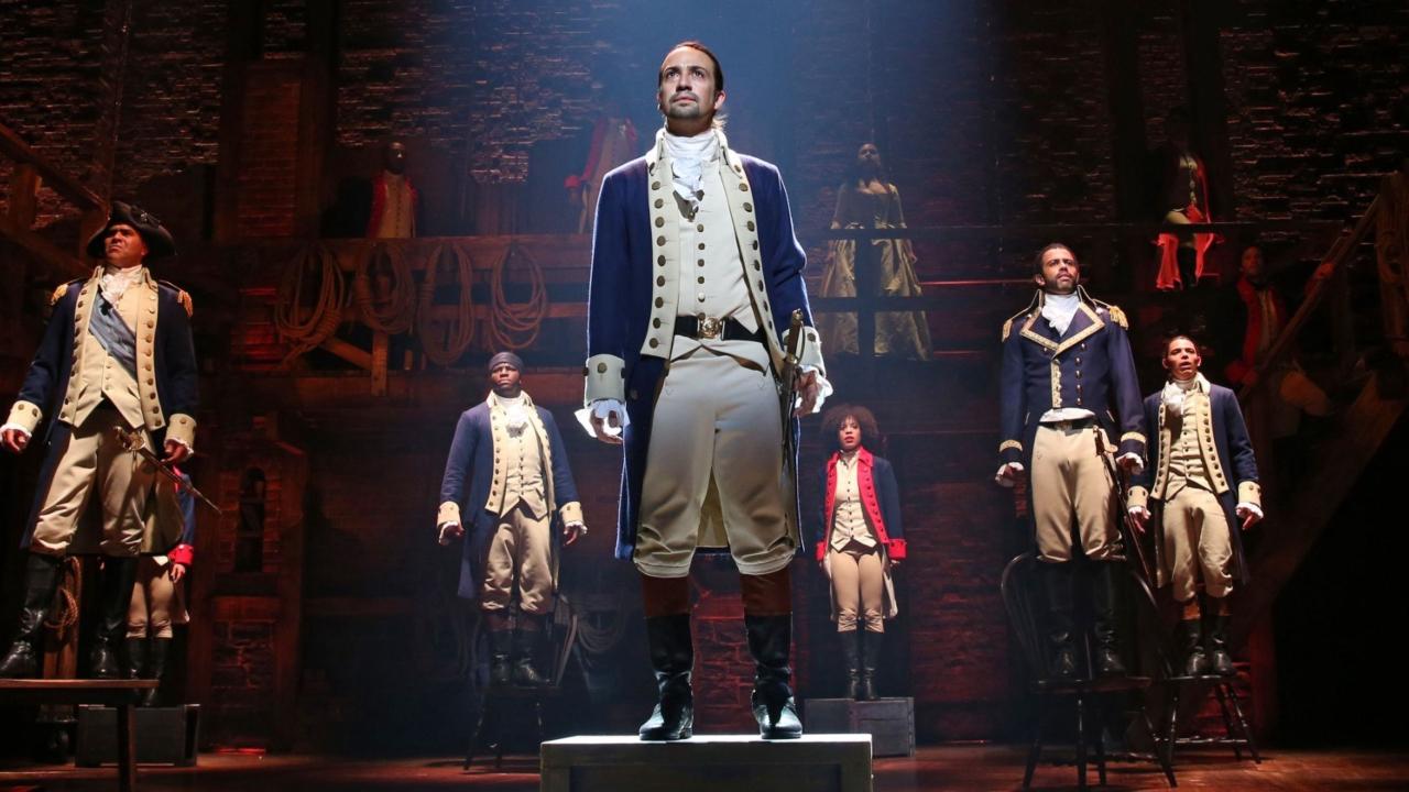 Cena do musical Hamilton. Na imagem, vemos o personagem Alexander Hamilton, com a vestimenta de cavaleiro branca e azul, sobre um tablóide, enquanto é iluminado por um feixe de luz. Logo atrás, outros seis cavaleiros estão sobre cadeiras espaçadas no palco. Todos olham para frente