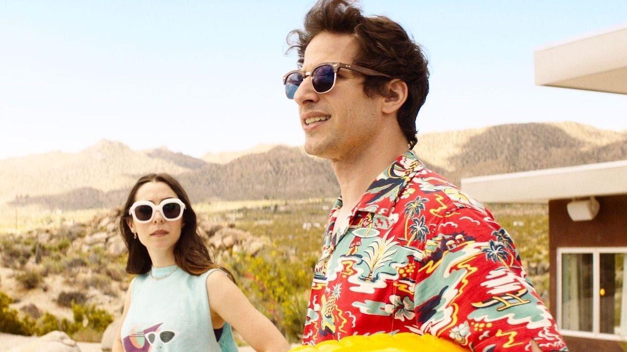 Cena do filme Palm Springs. Na esquerda, uma mulher de cabelos escuros até o ombro, com um óculos escuro de armação branca, ao seu lado um homem branco e moreno, também com óculos escuros, usando uma camisa vermelha florida. No fundo temos uma paisagem de montanha com céu azul e o começo de uma casa à direita.