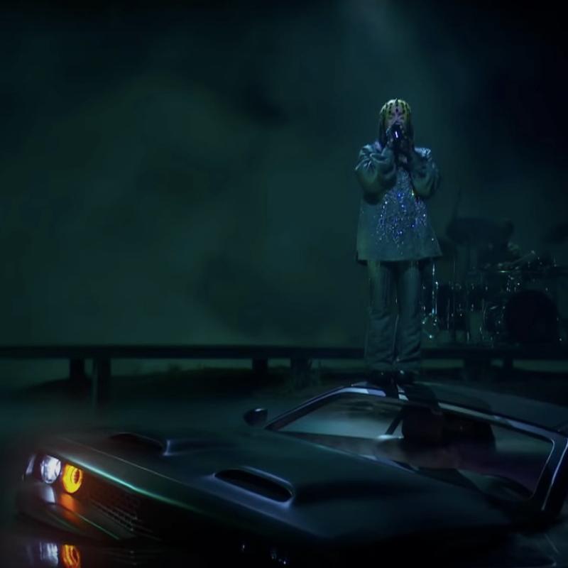 A imagem é uma foto da performance de Billie Eilish no Grammy 2021. No palco, Billie está cantando em cima de um carro, que parece estar se afogando. Billie é uma mulher branca, de cabelos verdes e pretos, ela veste uma blusa verde escura de mangas compridas e uma calça verde, e está com um acessório em sua cabeça. Ao fundo, ao lado esquerdo, é possível ver seu irmão e cantor FINNEAS ao teclado e, ao lado direito, há um baterista.