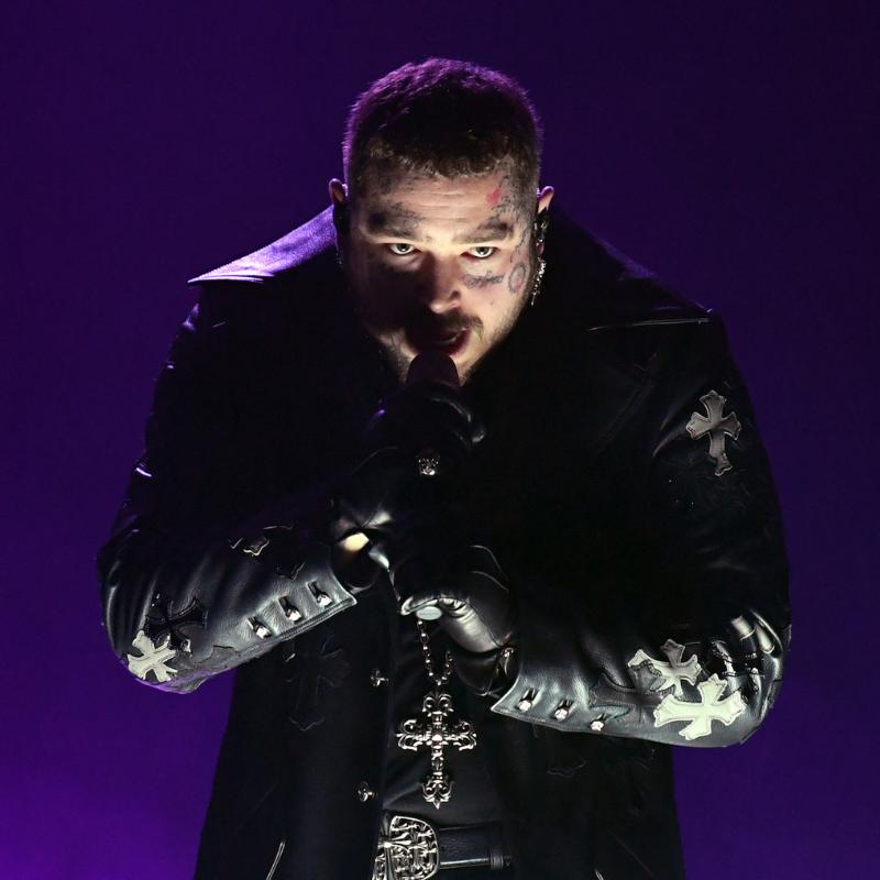 A imagem é uma foto da performance de Post Malone no Grammy 2021. Na foto, Post está segurando um microfone com as duas mãos. Post é um homem branco, de cabelos castanhos claros e curtos e tatuagens no rosto; ele veste uma jaqueta de couro preta com detalhes de cruz espalhados, uma camiseta preta e usa um colar com uma cruz.