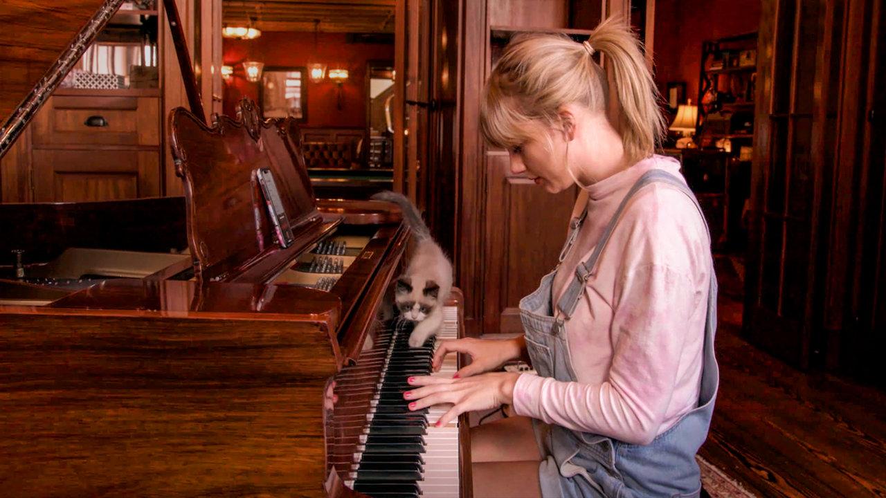 Cena do documentário Miss Americana, onde a cantora Taylor Swift - uma mulher branca de cabelos loiros que veste uma camiseta rosa e uma jardineira jeans - toca piano, enquanto seu gato - um filhote de pelagem que mescla branco e marrom - caminha sobre as teclas do instrumento. O piano tem tons de madeira, assim como o ambiente retratado na imagem.