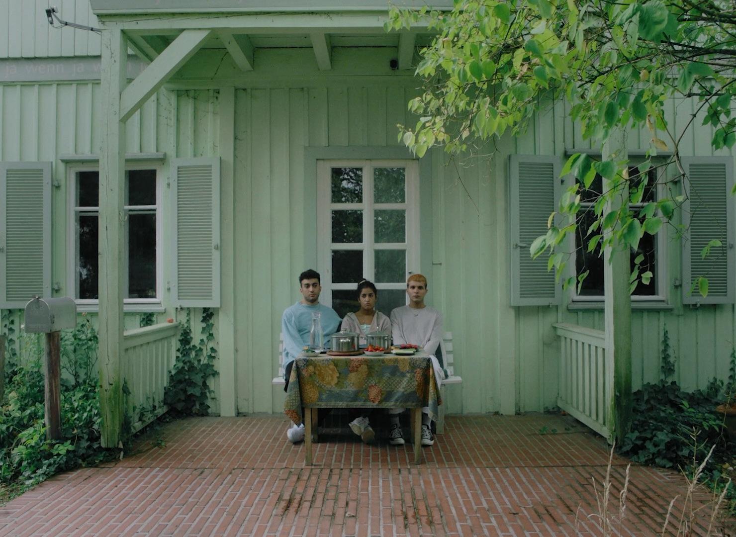 Cena do filme Sem Ressentimentos. Ao fundo, vemos uma casa de madeira verde. Próximos da parede estão sentadas três pessoas pardas, um homem, uma mulher, e outro homem. À frente deles está uma mesa, com panelas em cima. O chão é de tijolinhos.
