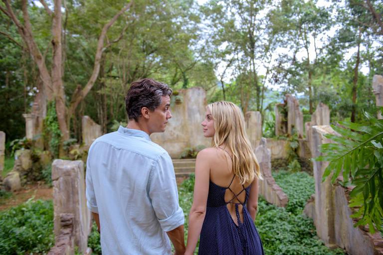 Foto da cena do filme Sergio, onde o ator Wagner Moura e a atriz Ana de Armas, que interpretam Sergio e Carolina na Cinebiografia, estão em ruínas no meio de uma floresta. Ambos se encontram de costas para a câmera e se encaram, de mãos dadas.