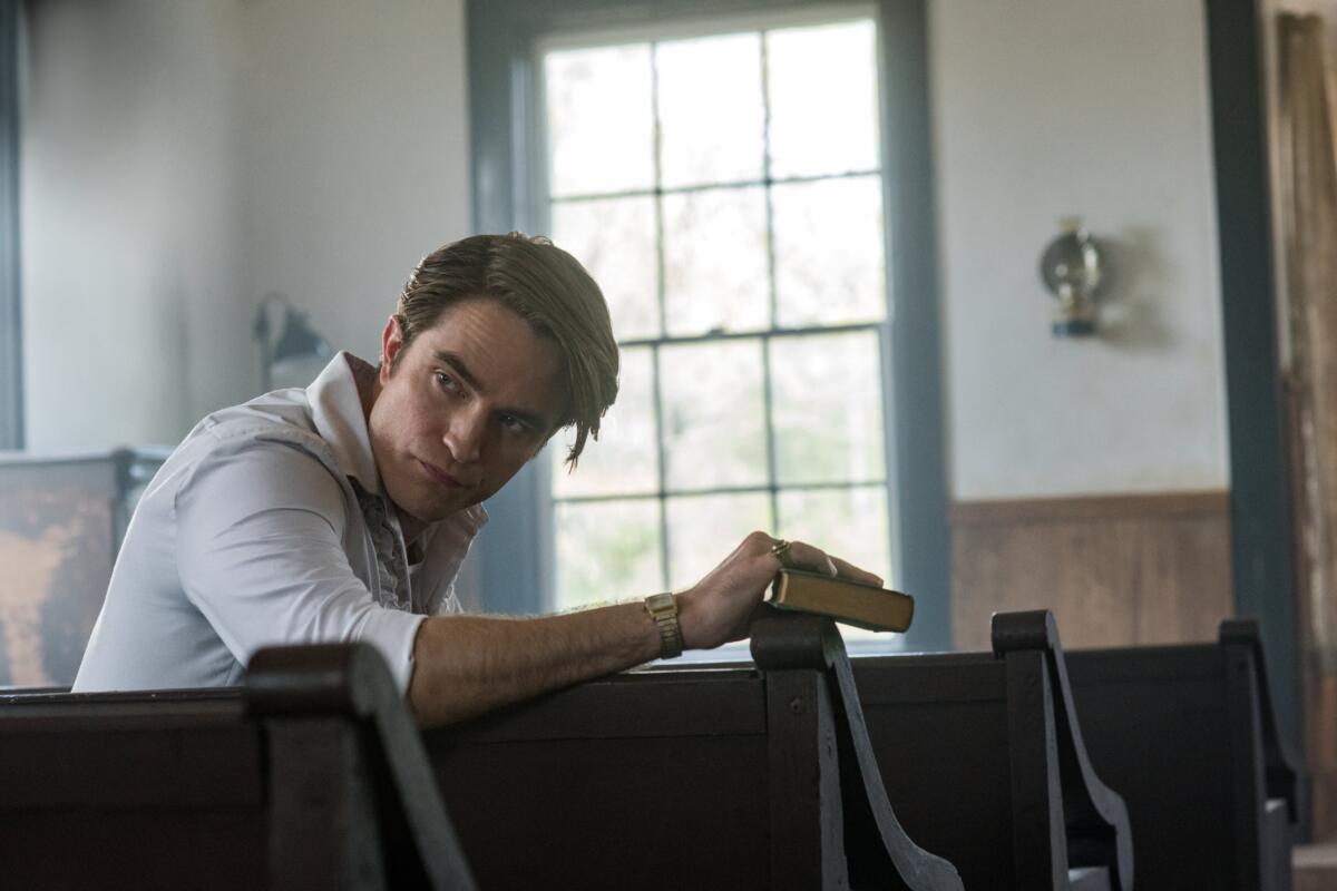 Cena do filme O Diabo de Cada Dia. Mostra o personagem de Robert Pattinson sentado em um banco de igreja. Ele tem metade do corpo virado e olha para trás. Em sua mão direita, que está apoiada nas costas do banco, ele segura um livro. O personagem é um homem branco de cabelos castanhos claros e curtos. Ele usa uma blusa social branca, um relógio de ouro no pulso e um anel no dedo mindinho. Ao fundo vemos uma grande janela desfocada e mais alguns bancos marrons.