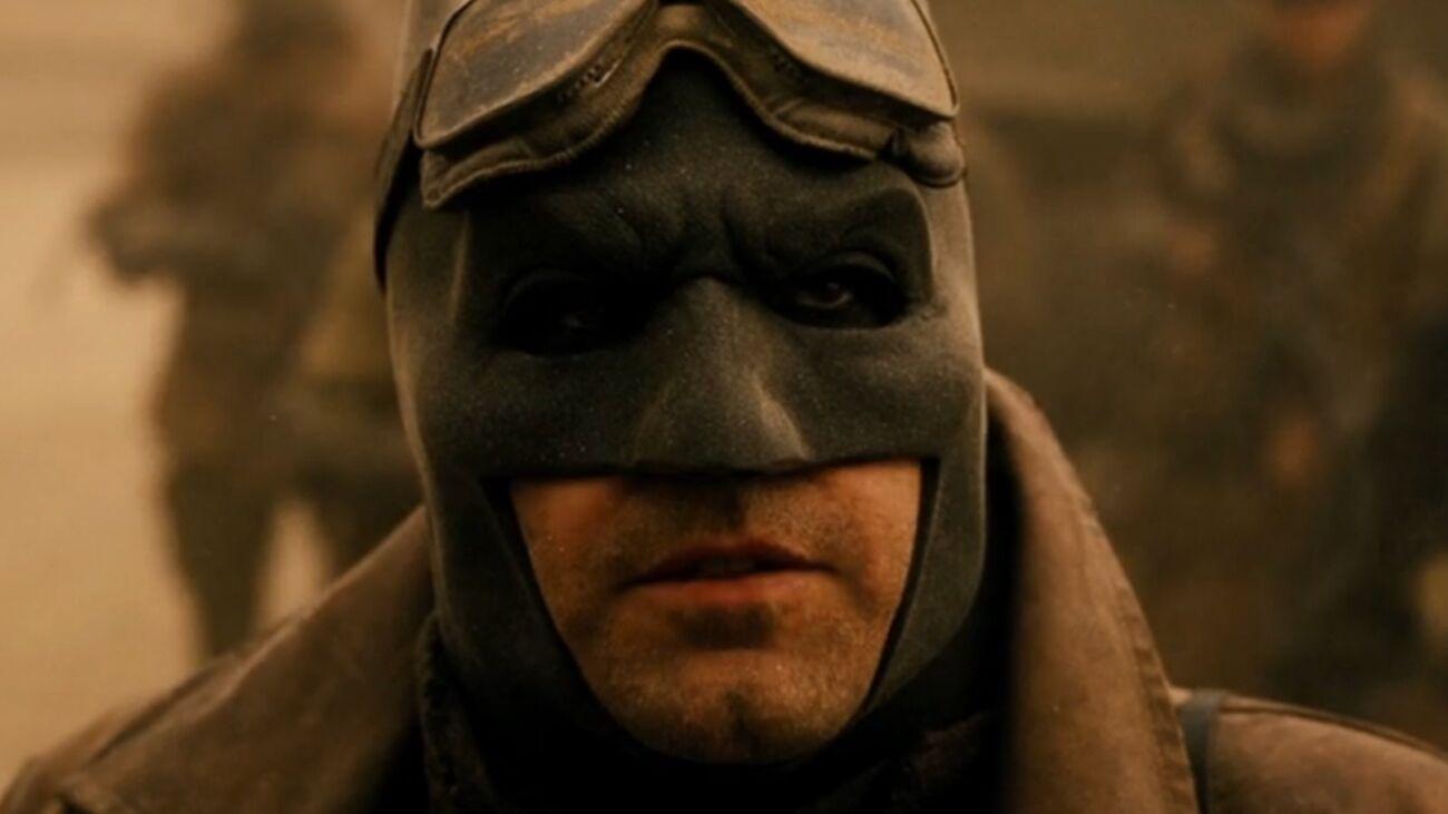 Cena do Snyder Cut. Na cena, vemos um close-up do Batman. Ele tem pele branca, e veste a máscara preto de borracha em formato de morcego. Acima da máscara, usa um óculos de aviador que está posicionado acima de seus olhos, na testa. Ele veste uma japona bege e o cenário é desértico.