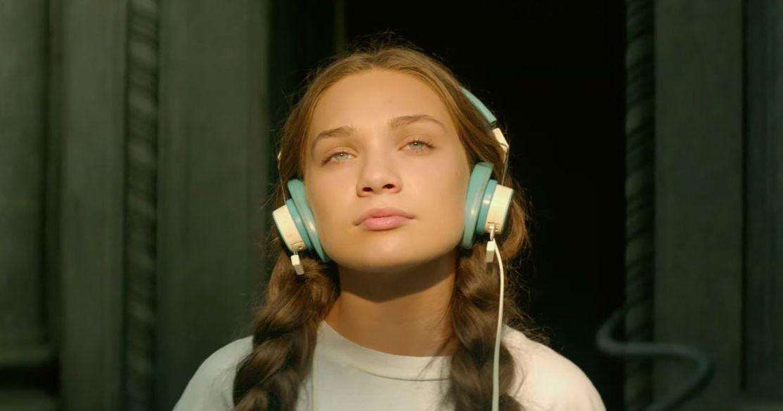 Cena do filme Music. Maddie Ziegler está no centro da imagem. Ela é uma garota branca, de cabelo castanho claro e comprido, preso em duas tranças. Ela usa um fone de ouvido azul e amarelo. Do busto para cima, usa uma camiseta branca. O sol bate levemente em seu rosto, e ela olha pra cima.