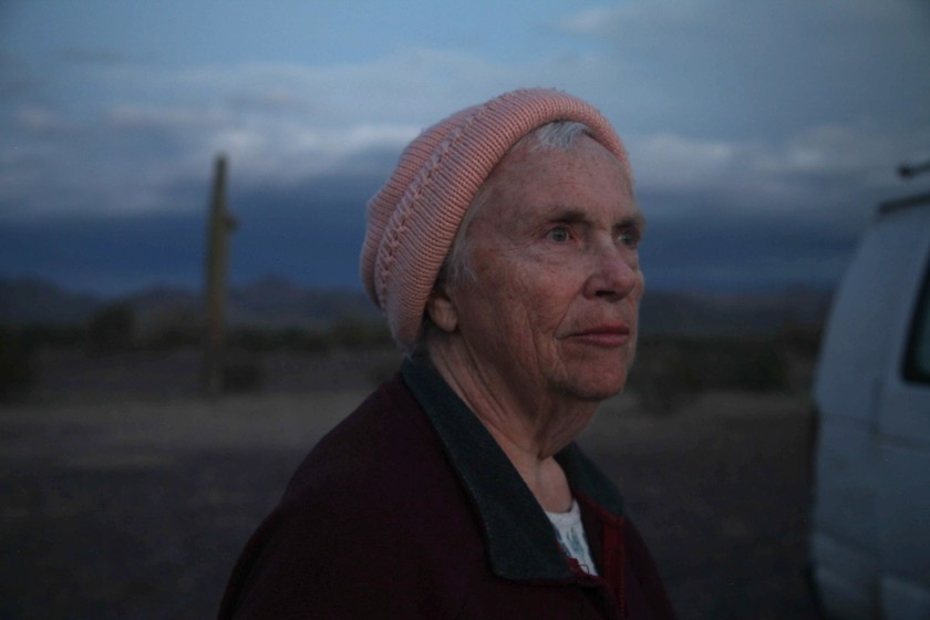 Cena do filme Nomadland. Nela, vemos Swankie, uma mulher branca, idosa e grisalha. Ela veste um gorro rosa e olha para o horizonte. Ao seu lado, está uma van desfocada e grama verde.