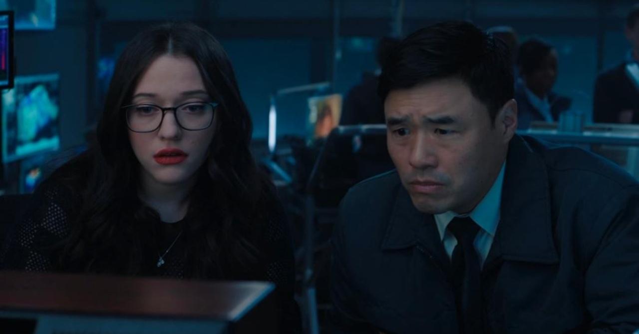 Cena da série WandaVision. Nela, vemos Darcy, vivida por Kat Dennings, e Jimmy Woo, interpretado por Randall Park. Eles estão dentro de uma sala e assistem a um monitor, lado a lado. À esquerda, está Darcy, uma mulher branca, de cabelos pretos e óculos de grau com armação quadrada escura. Jimmy é asiático, tem cabelos pretos e veste jaqueta azul com camisa branca e gravata escura por baixo.