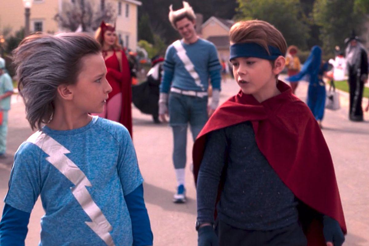 Cena da série WandaVision. Nela, vemos Tommy e Billy Maximoff. Ambos são brancos e tem cerca de 10 anos. Tommy, à esquerda, veste camiseta azul bebê com raio prateado de estampa, e tem o cabelo espetado para trás, com tons prateados. Billy usa banda azul, capa vermelha e camiseta azul. Ao fundo, vemos desfocados Wanda, de vermelho, e Pietro, também de azul.