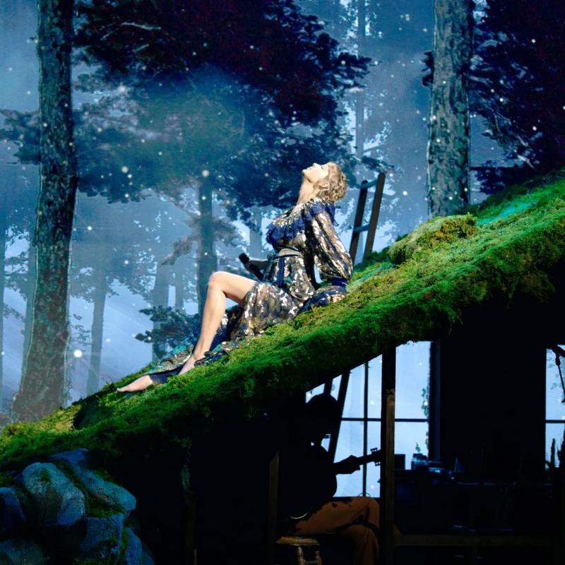 Imagem da apresentação de Taylor Swift no Grammy de 2021. A imagem mostra um solo verde suspenso e inclinado sobre o qual a cantora está sentada com a perna direita esticada e a esquerda flexionada. Ela tem as mão apoiadas atrás do corpo e a cabeça para cima. Taylor é uma mulher branca, de cabelos loiros presos em tranças ao redor da cabeça, e usa um vestido azul com detalhes em dourado. Ao fundo vemos uma floresta escura com alguns pontos de luz e abaixo do chão suspenso a silhueta de uma pessoa com um violão.