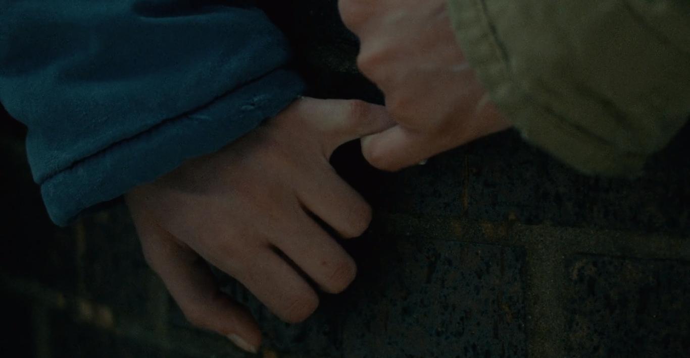 Cena do filme Nunca, Raramente, Às Vezes, Sempre. Duas mãos conectadas pelos mindinhos, apoiadas contra uma superfície de tijolos enegrecidos. Ambas as mãos são caucasianas, a da direita com uma manga bege e a da esquerda com uma manga azul.