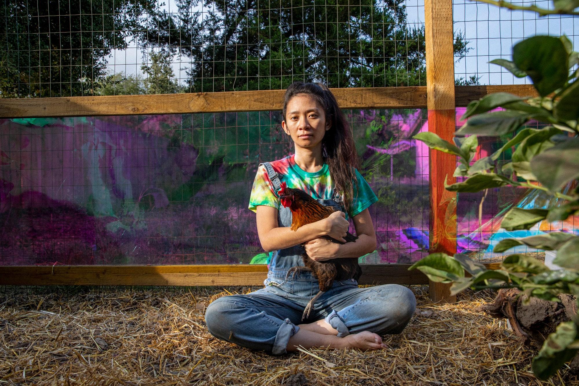 A diretora está Chloé Zhao sentada no chão segurando uma galinha marrom. Ela é uma mulher adulta, chinesa, de cabelos presos e olha para a câmera. Veste uma camiseta tie-dye colorida e um macacão jeans. Ao seu redor, vemos mato e folhas, e uma cerca marrom atrás dela.