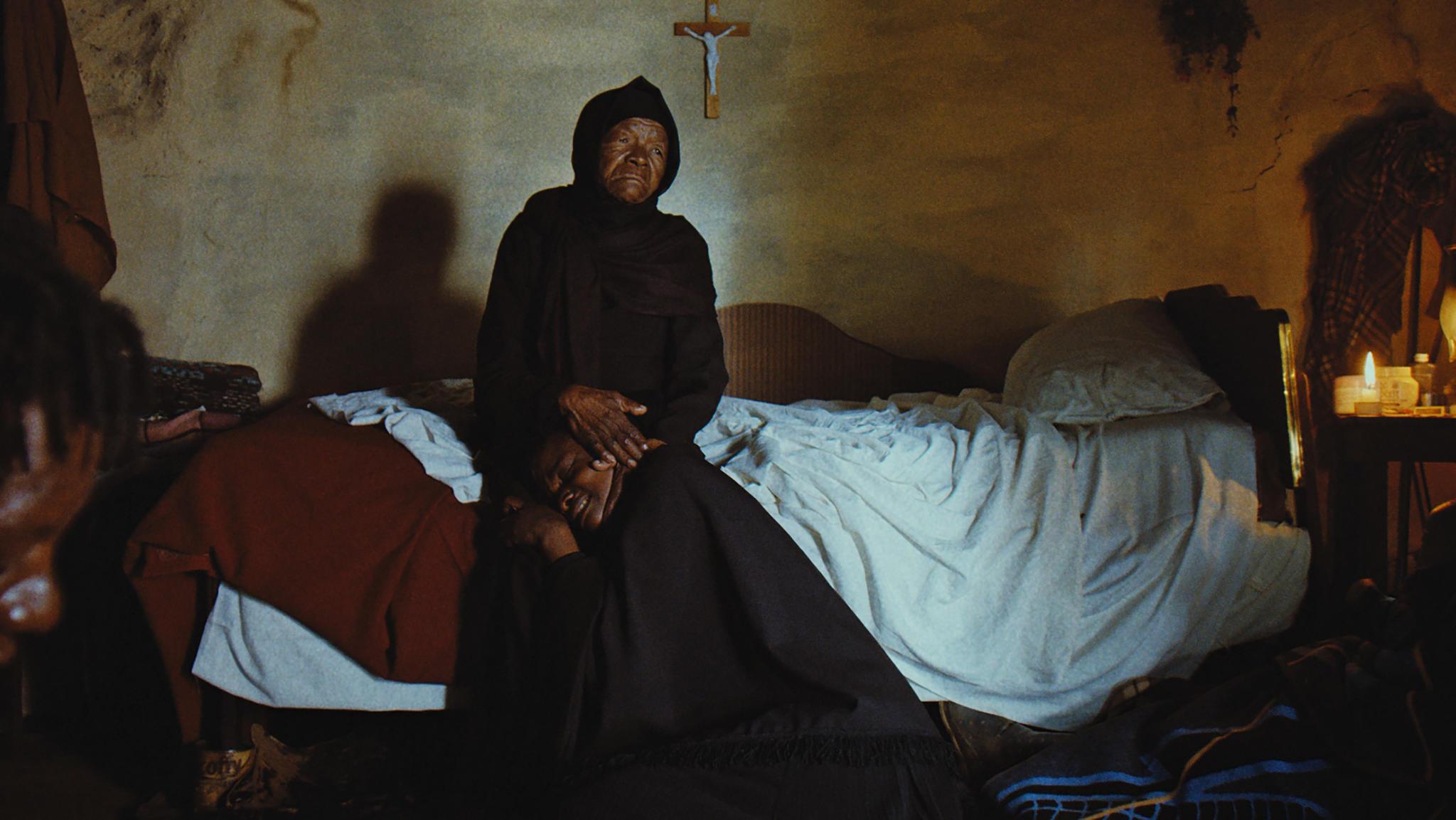 Cena do filme Isso Não É um Enterro, É uma Ressurreição. Mary Twala, uma senhora negra de 80 anos, está vestida toda de preto, com um vestido que cobre até a cabeça. Ela está sentada em uma cama com lençol branco e, no seu colo, está apoiada uma mulher negra e jovem de uns 30 anos. A mulher chora e está vestida com uma roupa preta que a cobre por inteiro. Ao fundo, na parede bege marcada, está pendurado um crucifixo com Jesus.