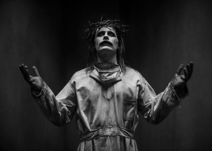 Foto de Jared Leto caracterizado como o Coringa do Snyder Cut. A foto é em preto e branco, ele veste um manto branco, e tem as mãos levantadas em uma espécie de sinal religioso, ele tem cabelos compridos, a boca pintada e usa uma coroa de espinhos, numa alusão bíblica.
