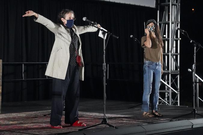 Frances e Chloe num palco, usando máscaras e falando no microfone. Frances está de bege, máscara preta e braços abertos. Chloé está no canto, de boné escuro e máscara camuflada preto e branco. Ela olha para Frances e está de noite