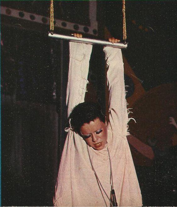 Fotografia de Elis Regina no espetáculo Falso Brilhante. Na imagem, a artista segura uma barra com as mãos e parece estar pendurada. Ela olha para baixo, com os olhos quase fechados, e veste uma roupa branca.