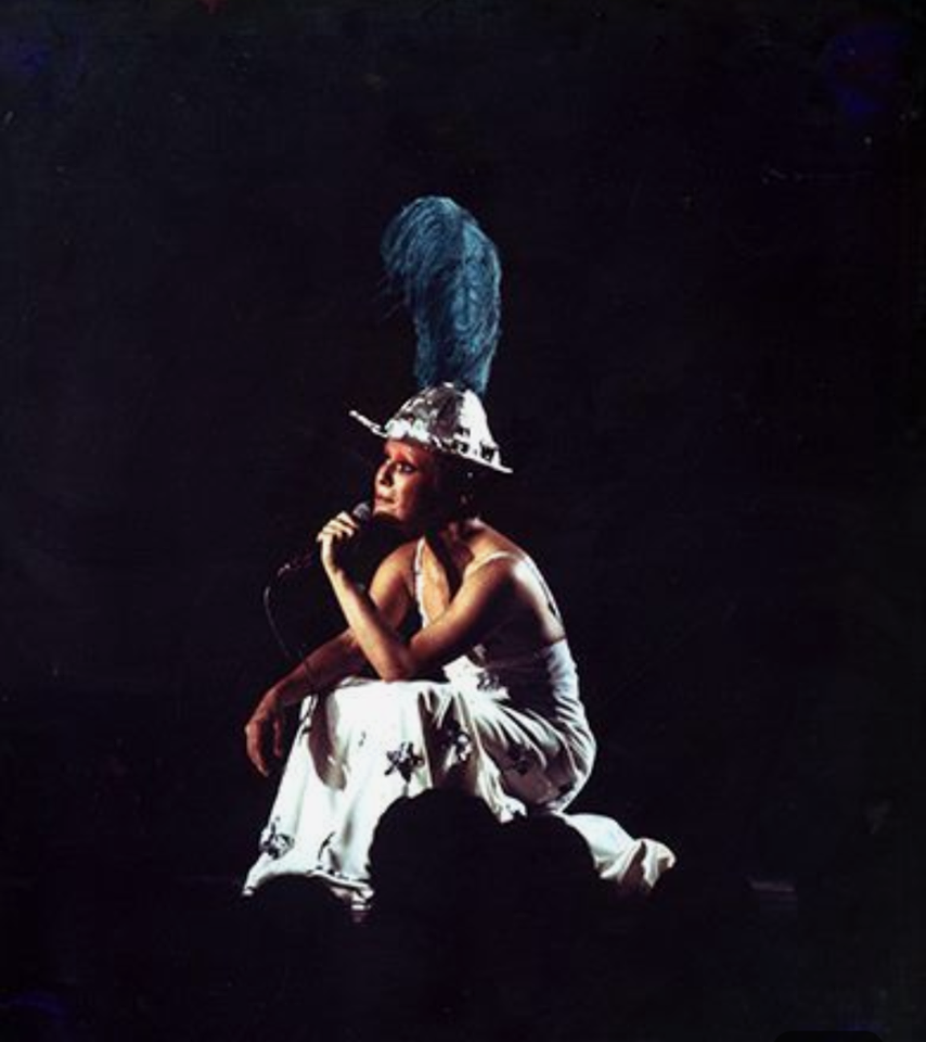 Fotografia de Elis Regina apresentando seu espetáculo Falso Brilhante. A artista está sentada no palco, ao centro da imagem, e apenas ela está iluminada. Ela está de lado, segura um microfone com a mão esquerda e olha para o lado esquerdo da imagem. Elis usa um vestido branco come strelas prateadas e um chapéu com uma pena azul.