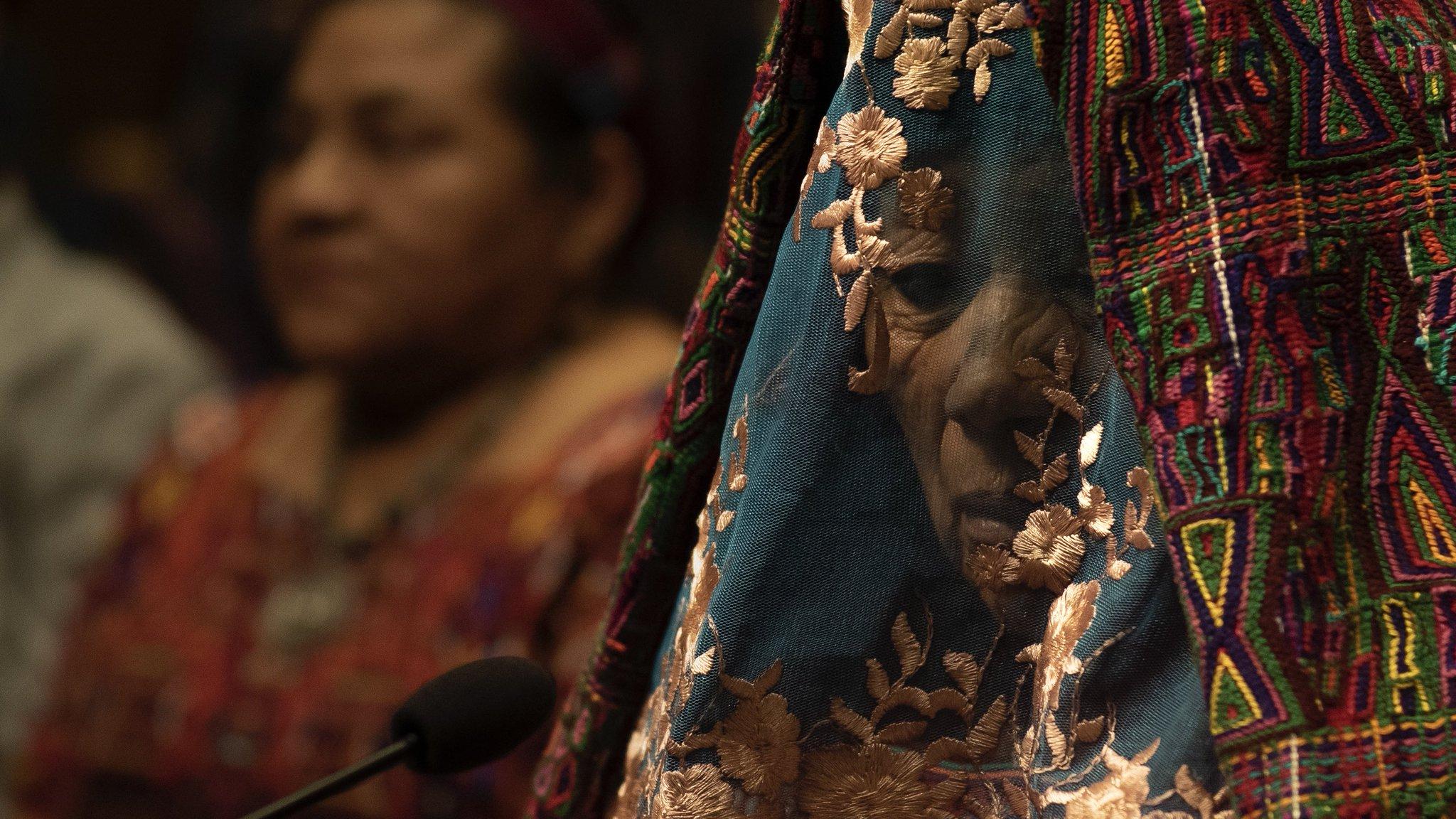 Cena do filme La Llorona. À frente e à direita, uma senhora com o rosto parcialmente coberto por um véu de padrões nativos, com cores vivas, que variam entre azul, roxo, verde e vermelho e detalhes floridos. Possui uma feição triste e aguarda em frente a um microfone. Atrás e à sua esquerda vemos uma imagem desfocada de Rigoberta Menchú, uma mulher indígena, com um colar e uma blusa laranja florida.