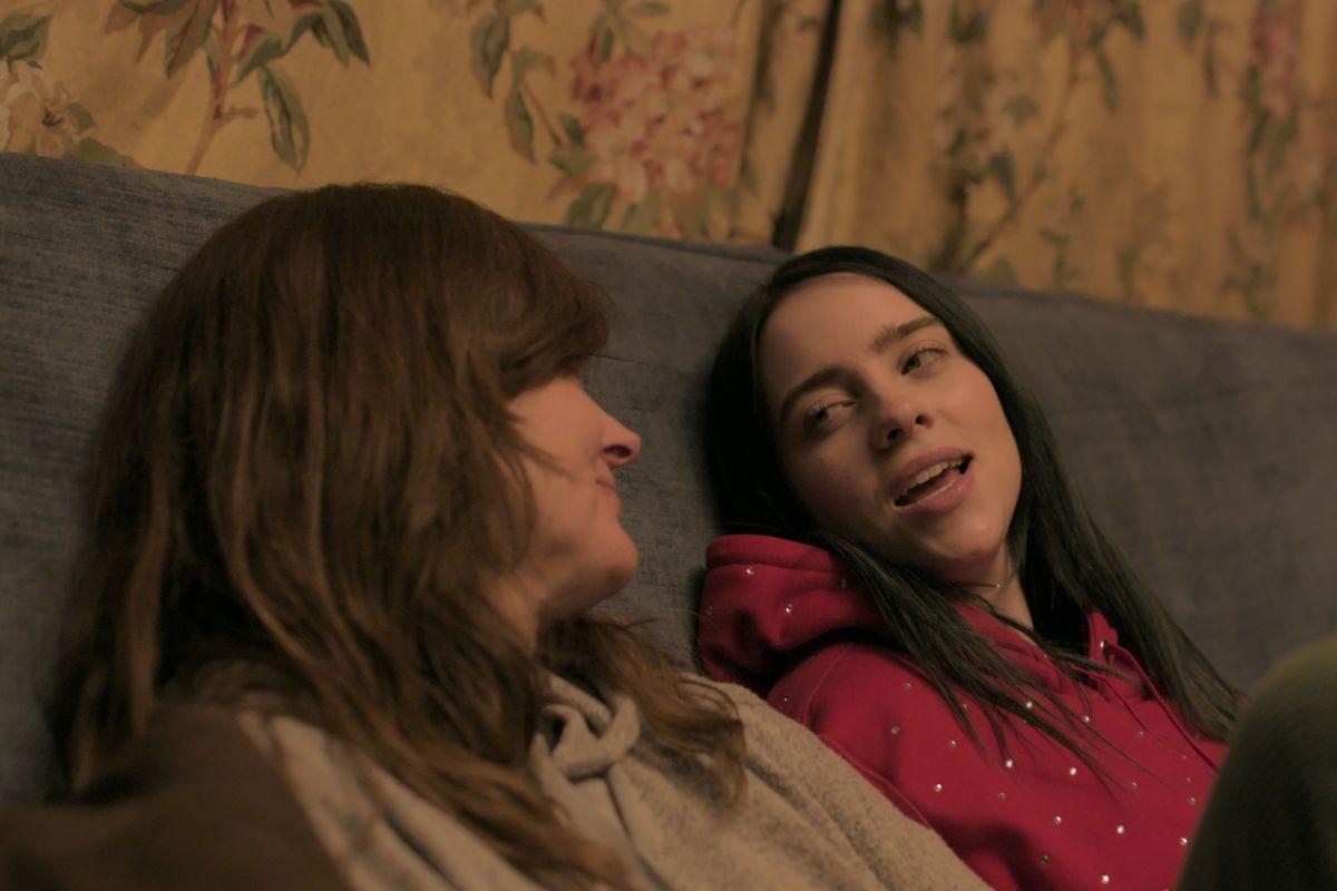 Cena do documentário Billie Eilish: The World's A Little Blurry. Na imagem, Billie Eilish e sua mãe estão sentadas em um sofá. À esquerda, está a mãe de Billie, uma mulher branca de cabelos longos e castanhos claros, ela veste uma blusa cinza e está com o rosto virado em direção à filha. À direita, está Billie Eilish, uma mulher branca de cabelos castanhos escuros e compridos, ela veste um moletom vermelho e está falando com o rosto virado em direção à mãe.