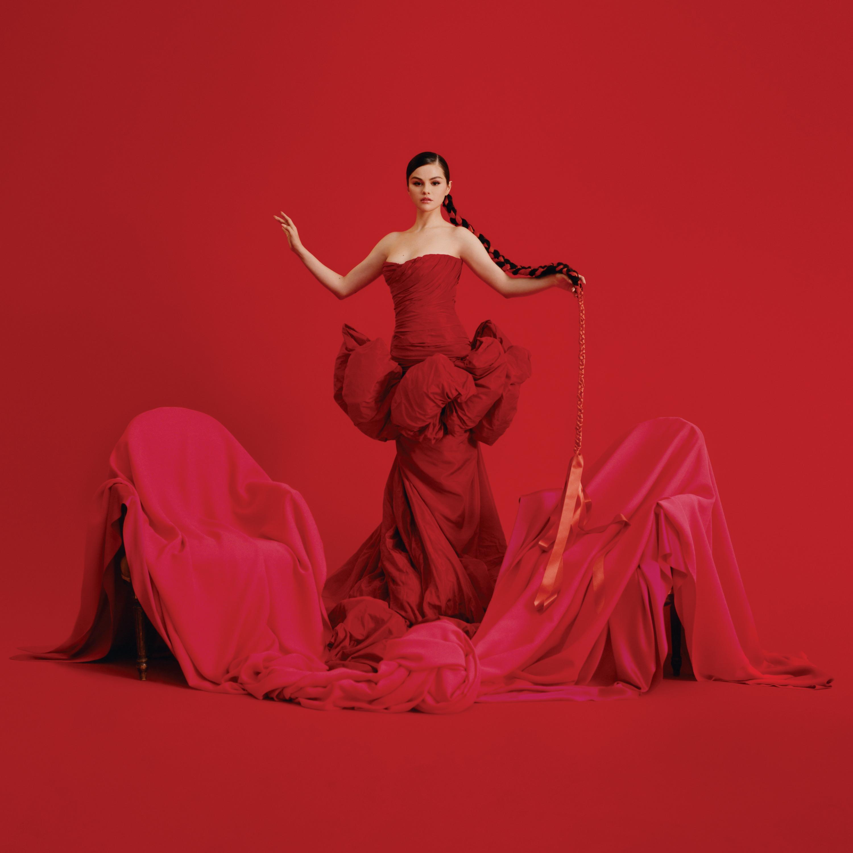 Selena Gomez, uma mulher branca de cabelo castanho, está em pé, usando um vestido vermelho com babados na cintura. Ela está com uma trança no cabelo. Essa trança está com uma fita vermelha, que vai até as pontas do cabelo e com um caimento de fita abaixo. No chão, existem duas cadeiras, cobertas por um pano vermelho. O fundo da imagem também é todo vermelho.