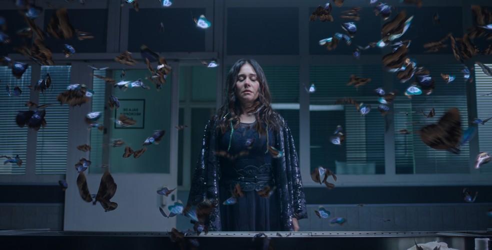 Cena da série Cidade Invisível. Nela vemos a atriz Alessandra Negrini, uma mulher adulta, branca e com cabelo castanho comprido. Ela usa um vestido azul e uma capa com diversos detalhes. Ao redor da atriz há várias borboletas na cor azul voando. Essa cena ocorre dentro de uma sala de necrotério na cor cinza, com detalhes em azul-escuro e com as janelas e porta de vidro.