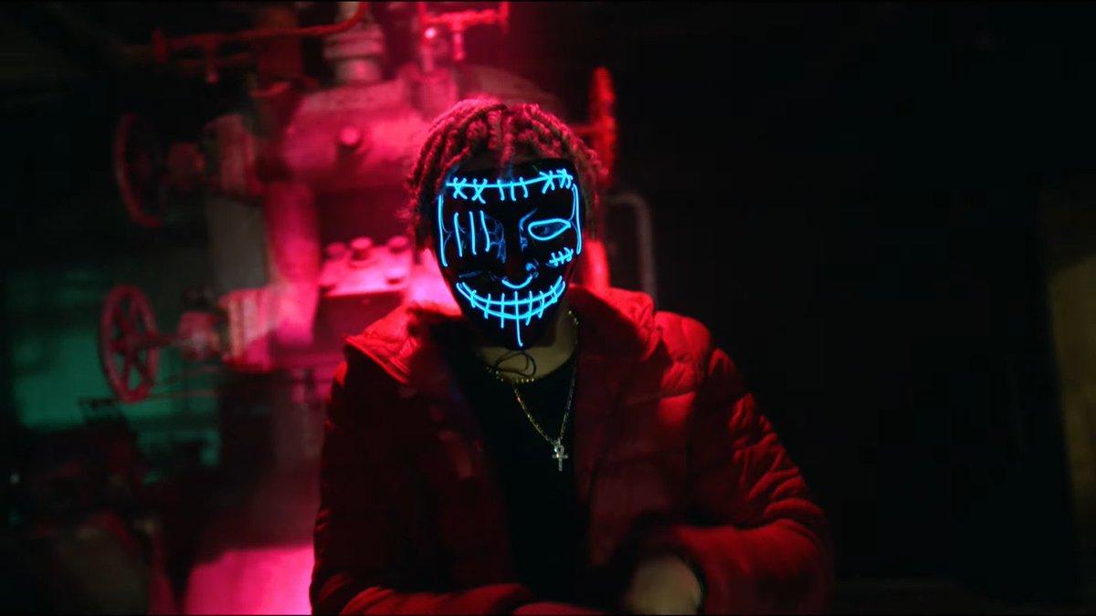 A imagem é uma cena do videoclipe da música Come Around Me, de Justin Bieber. Nela, há um menino com uma máscara preta, com luz led na cor azul. Ele possui dreads no cabelo e veste um casaco vermelho, uma blusa preta e uma corrente no pescoço.