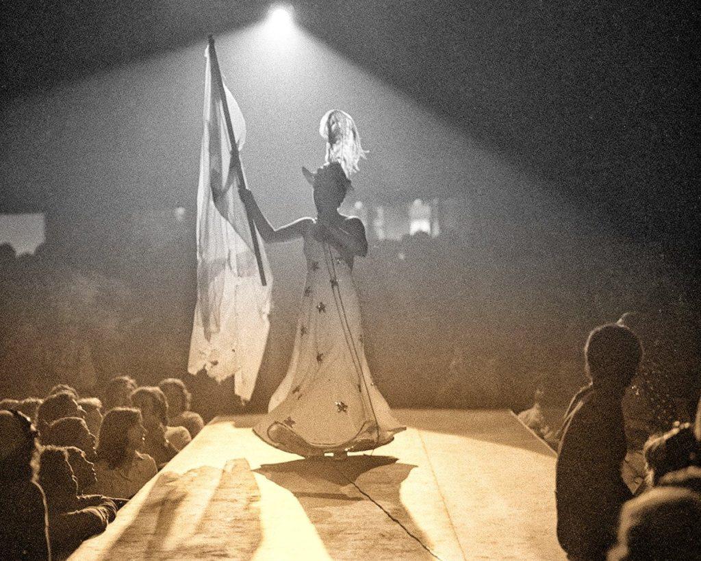 Fotografia de Elis Regina apresentando seu espetáculo Falso Brilhante. A artista está ao centro da imagem, numa passarela, cercada pelo público. Ela está de frente para a câmera mas contra a luz, que impede de exergarmos seu rosto. Ela segura uma bandeira grande na mão direita e um microfone na mão esquerda. Elis usa um vestido lingo, branco, de alças finas e estampado por estrelas prateadas. Ela também usa uma chapéu com uma pena grande e seus cabelos são curtos. A fotografia está colorida em tons de amarelo e um cinza azulado.